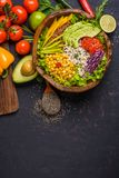 Wooden bowl with chickpea, avocado, wild rice, quinoa, bell pepper, tomatoes, greens, cabbage, lettuce on dark stone table and. Wooden bowl with chickpea royalty free stock photos