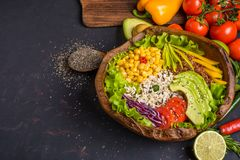 Wooden bowl with chickpea, avocado, wild rice, quinoa, bell pepper, tomatoes, greens, cabbage, lettuce on dark stone table and. Wooden bowl with chickpea stock photography