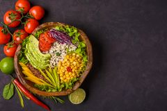 Wooden bowl with chickpea, avocado, wild rice, quinoa, tomatoes, greens, cabbage, lettuce on dark stone background. Vegetarian. Superfood. Top view copy space stock image