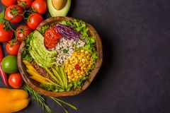Wooden bowl with chickpea, avocado, wild rice, quinoa, tomatoes, greens, cabbage, lettuce on dark stone background. Vegetarian. Superfood. Top view copy space royalty free stock photo