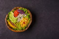 Wooden bowl with chickpea, avocado, wild rice, quinoa, tomatoes, greens, cabbage, lettuce on dark stone background. Vegetarian. Wooden bowl with chickpea royalty free stock photography