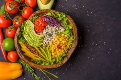 Wooden bowl with chickpea, avocado, wild rice, quinoa, tomatoes, greens, cabbage, lettuce on dark stone background. Vegetarian. Superfood. Top view copy space stock photography