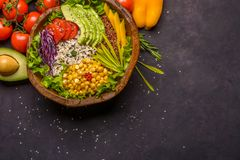 Wooden bowl with chickpea, avocado, wild rice, quinoa, tomatoes, greens, cabbage, lettuce on dark stone background. Vegetarian. Superfood. Top view copy space royalty free stock images