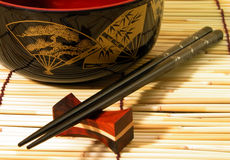 Wooden bowl and chopsticks. On a bamboo straws floor Stock Image