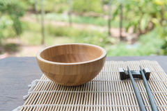 Wooden bowl with chopsticks on bamboo mat  on wooden table in the garden.  Stock Image