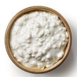 Wooden bowl of chunky cottage cheese isolated on white from abov. E Royalty Free Stock Images