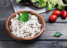 Wooden bowl with cooked white long-grain and wild rice. Parsley, lettuce, cherry tomatoes on a gray wooden background stock images