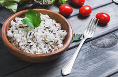 Wooden bowl with cooked white long-grain and wild rice. Parsley, lettuce, cherry tomatoes on a gray wooden background royalty free stock photo