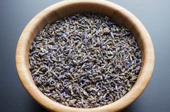Dry lavender tea. Wooden bowl with dried lavender tea over grey background stock images