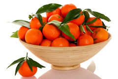 Wooden bowl filled with fresh orange mandarin citrus fruit with Royalty Free Stock Photography