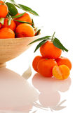 Wooden bowl filled with fresh orange mandarin citrus fruit with Stock Photo