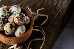Wooden bowl filled with quail eggs on wooden board over white background, close-up, selective focus. Wooden bowl filled with fresh quail eggs and some hay on Stock Photography