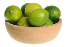 Wooden bowl filled with limes Royalty Free Stock Image