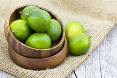 Wooden bowl filled with limes Royalty Free Stock Photo