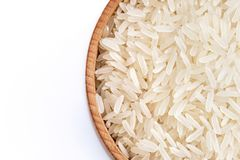 Wooden bowl filled parboiled rice on white background. Stock Image