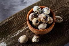 Wooden bowl filled with quail eggs on wooden board over white background, close-up, selective focus. Wooden bowl filled with fresh quail eggs and some hay on Royalty Free Stock Images