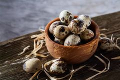 Wooden bowl filled with quail eggs on wooden board over white background, close-up, selective focus. Wooden bowl filled with fresh quail eggs and some hay on Stock Images