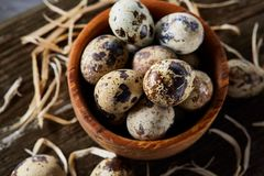 Wooden bowl filled with quail eggs on wooden board over white background, close-up, selective focus. Wooden bowl filled with fresh quail eggs and some hay on Stock Photo