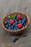 Wooden bowl with fresh blueberries and raspberries, vertical. Close-up Stock Photography
