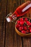 Wooden bowl full of cherries and red lemonade Stock Image