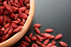 Wooden Bowl Full of Dried Goji Berries on the Black Table Royalty Free Stock Images