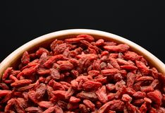 Wooden Bowl Full of Dried Goji Berries on the Black Table Royalty Free Stock Photo