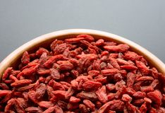 Wooden Bowl Full of Dried Goji Berries on the Dark Table Stock Image