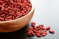 Wooden Bowl Full of Dried Goji Berries on the Dark Table Royalty Free Stock Image