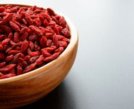 Wooden Bowl Full of Dried Goji Berries on the Dark Table Stock Images