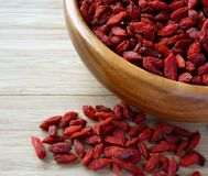 Wooden Bowl Full of Dried Goji Berries on the Table Stock Photo