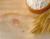 Wooden bowl full flour and wheat ears Royalty Free Stock Images