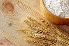 Wooden bowl full flour and wheat ears Royalty Free Stock Photo