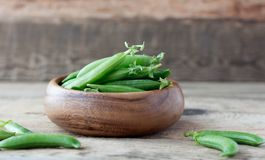 Wooden bowl full  of green peas pods. Wooden bowl full of fresh pods of green peas on old wooden background Stock Photo