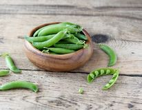 Wooden bowl full  of green peas pods. Wooden bowl full of fresh pods of green peas on old wooden background Royalty Free Stock Photo