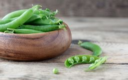 Wooden bowl full  of green peas pods Royalty Free Stock Photos