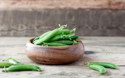 Wooden bowl full  of green peas pods. Wooden bowl full of fresh pods of green peas on old wooden background Stock Images