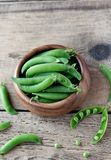 Wooden bowl full  of green peas pods. Top view. Top view of wooden bowl full of fresh pods of green peas on old wooden background Royalty Free Stock Image