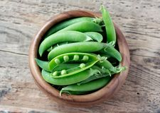 Wooden bowl full  of green peas pods. Top view. Top view of wooden bowl full of fresh pods of green peas on old wooden background Royalty Free Stock Photo