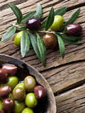 Wooden bowl full of olives and olive twigs. stock image