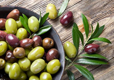 Wooden bowl full of olives and olive twigs. royalty free stock photo