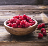 Wooden bowl full of ripe juicy fragrant garden raspberries on  simple rustic  background. View from above. Horizontal Royalty Free Stock Photo
