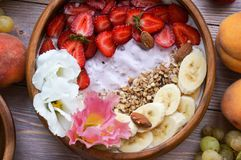 Wooden bowl with granola and fruits royalty free stock images
