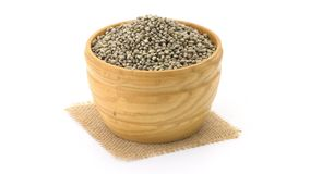 Wooden bowl with hemp seeds. Loopable video of a wooden bowl with hemp seeds rotating clockwise on a piece of burlap cloth with white background obliquely from stock footage