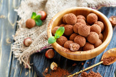 Wooden bowl of homemade chocolates filled with hazelnut. Stock Image
