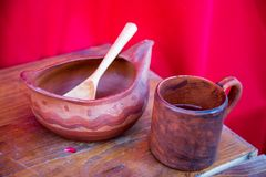 Wooden bowl mug spoon mahogany painted with a simple pattern on a red background. Selective focus. Folk wooden art. Leisure Hobbies royalty free stock photos
