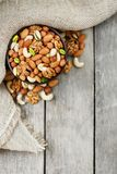 Wooden bowl with nuts on a wooden background, near a bag from burlap. Healthy food and snack, organic vegetarian food. Walnut, pistachios, almonds, hazelnuts stock photography