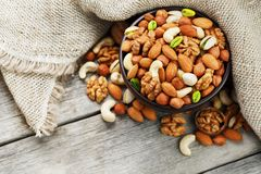 Wooden bowl with nuts on a wooden background, near a bag from burlap. Healthy food and snack, organic vegetarian food. Walnut, pistachios, almonds, hazelnuts royalty free stock photo
