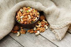 Wooden bowl with nuts on a wooden background, near a bag from burlap. Healthy food and snack, organic vegetarian food. Walnut, pistachios, almonds, hazelnuts stock images