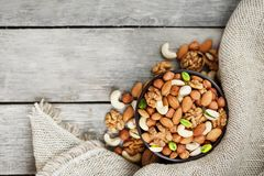 Wooden bowl with nuts on a wooden background, near a bag from burlap. Healthy food and snack, organic vegetarian food. Walnut, pistachios, almonds, hazelnuts stock photos