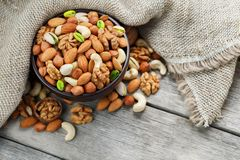 Wooden bowl with nuts on a wooden background, near a bag from burlap. Healthy food and snack, organic vegetarian food. Walnut, pistachios, almonds, hazelnuts royalty free stock photography